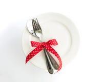 Fourchette d'arrangement de dîner d'amour et lien de cuillère avec le ruban rouge du plat Photographie stock libre de droits