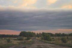 Fourchette de chemin de terre de pays de soirée Mauvaises routes dans l'hinterland rural Paysage nuageux rustique de coucher du s photos stock