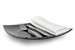 Fourchette de couteau de plaque noire et une serviette Photographie stock