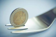 Fourchette en métal avec la pièce de monnaie de l'euro deux comme symbole de la crise Photographie stock