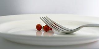 Fourchette et baies d'une plaque blanche Photos stock