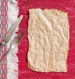 Fourchette et couteau de vintage sur la serviette sur le bois et le papier rouges de métier Photo libre de droits