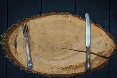 Fourchette et couteau sur un cadre en bois, l'espace vide au milieu Photos stock