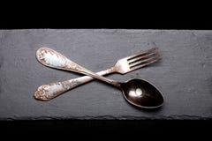 Fourchette et cuillère d'un plat d'ardoise sur un fond noir photographie stock