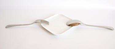 Fourchette et cuillère d'une plaque et d'un blanc blancs Image libre de droits