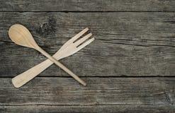 Fourchette et cuillère en bois croisées sur le fond rustique Photo libre de droits