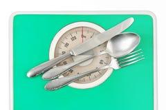 Fourchette et cuillère sur l'échelle de poids image stock