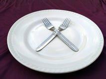 Fourchette et cuill?re dans le plat blanc d'isolement sur un fond violet photo stock