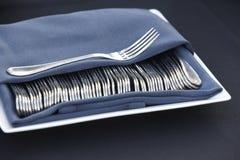 Fourchettes classiques couvertes de serviette bleue au-dessus d'un plat Images stock