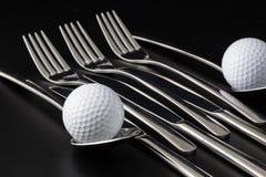 Fourchettes, cuillères et couteaux et boules de golf Photos stock