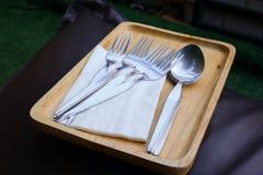 Fourchettes, cuillères, et papiers de soie de soie sur le plateau en bois image stock
