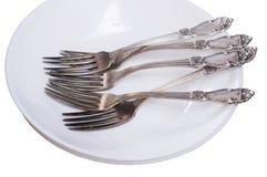 Fourchettes dans un plat blanc vide Photographie stock
