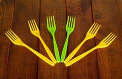 Fourchettes en plastique colorées jetables sur le fond du bois foncé Photo libre de droits