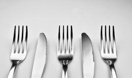 Fourchettes et couteaux d'isolement sur le fond gris Photographie stock