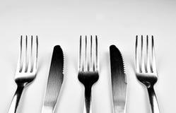 Fourchettes et couteaux d'isolement sur le fond lumineux Image libre de droits