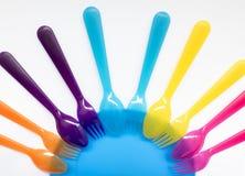 Fourchettes et cuillères en plastique colorées, d'un plat, le fond dessus Photos stock