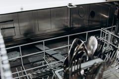 Fourchettes et cuill?res s?ches propres dans un plan rapproch? ouvert de lave-vaisselle plan rapproch? de compartiment de couvert photo libre de droits