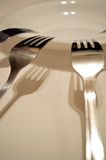 Fourchettes et ombres sur le fond blanc Image stock