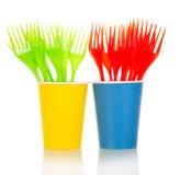 Fourchettes jetables colorées en plan rapproché en verre sur le blanc Image stock