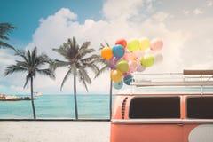 fourgon avec le ballon coloré sur le ciel bleu de plage Photo stock