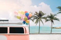 fourgon avec le ballon coloré sur le ciel bleu de plage Photo libre de droits