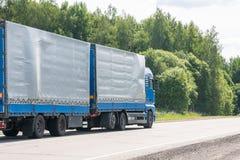 Fourgon de livraison bleu et camion blanc conduisant sur la route goudronnée entre la ligne des arbres dans le paysage d'automne photo stock
