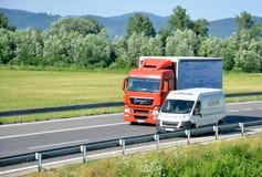 Fourgon de n de Citroà blanc le «rattrape le camion d'HOMME rouge sur la route du slovak D1 dans la campagne Photo libre de droits