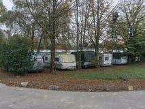 Fourgons et camions se tenant sur une pelouse couverte de feuilles d'automne jaunes photo stock