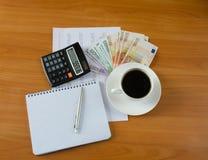 Fournitures de bureau avec l'argent et la tasse de café Photographie stock libre de droits