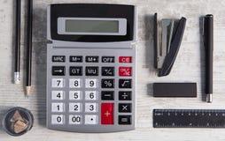 Fournitures de bureau de calculatrice sur le fond en bois photographie stock