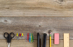 Fournitures de bureau de base d'école ou sur les conseils en bois rustiques Photographie stock libre de droits