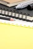 Fournitures de bureau, marqueurs, carnet et papier sur le backgroun jaune Photographie stock libre de droits