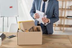 Fournitures de bureau mises le feu d'emballage d'homme d'affaires dans la boîte en carton sur le lieu de travail Photographie stock