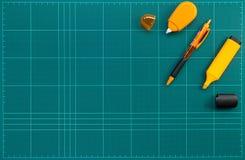 Fournitures de bureau oranges sur le tapis vert de coupe, photo plate de configuration images stock