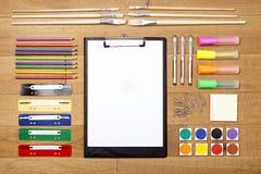 Fournitures de bureau sur le plancher en bois, presse-papiers avec le papier vide Photos stock