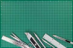 Fournitures de bureau sur le tapis de coupe - coupeurs, ciseaux, p mécanique Images stock