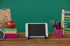 Fournitures scolaires avec le comprimé numérique sur la table en bois Images libres de droits