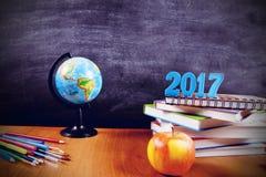 Fournitures scolaires avec les numéros 2017 sur une pile de livres et une pomme sur le fond de tableau noir avec le copyspace pou Photographie stock