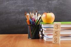 Fournitures scolaires avec une pile de livres et une pomme sur le fond de tableau noir avec le copyspace pour votre texte, concep Image stock