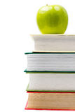 Fournitures scolaires dans la salle de classe avec des livres et la pomme sur le blanc Images stock