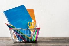 Fournitures scolaires dans un panier sur une table en bois Image stock