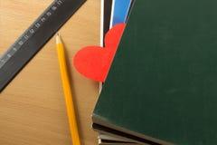 Fournitures scolaires et coeur rouge de papier sur une table Images libres de droits