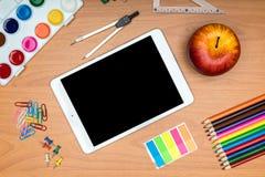 Fournitures scolaires et comprimé sur le bureau en bois d'école d'en haut Photographie stock libre de droits