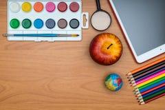 Fournitures scolaires et comprimé sur le bureau en bois d'école d'en haut Images stock