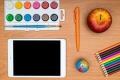 Fournitures scolaires et comprimé sur le bureau en bois d'école d'en haut Images libres de droits