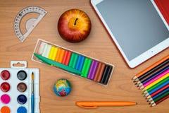 Fournitures scolaires et comprimé sur le bureau en bois d'école d'en haut Image stock