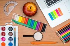 Fournitures scolaires et comprimé sur le bureau en bois d'école d'en haut Photo libre de droits