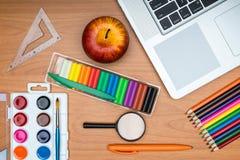 Fournitures scolaires et comprimé sur le bureau en bois d'école d'en haut Photo stock