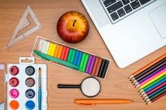 Fournitures scolaires et comprimé sur le bureau en bois d'école d'en haut Photos stock