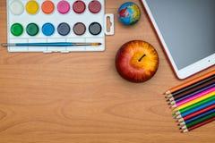 Fournitures scolaires et comprimé sur le bureau en bois d'école d'en haut Photographie stock